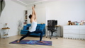 Young woman practicing yoga at home, standing in warrior position 73244939