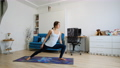 Young woman practicing yoga at home, stretching arm and leg 73260750