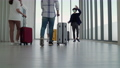 Amid the coronavirus outbreak, masked tourists greet each other in airport lounges. 73266044