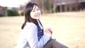 一個女人坐在公園的草地上唱歌(慢) 73277945