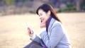 一個女人坐在公園的草地上唱歌(慢) 73277946