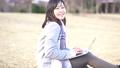 一個女人坐在公園的草坪上,使用一台筆記本電腦 73285702