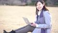 一個女人坐在公園的草坪上,使用一台筆記本電腦 73285703