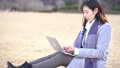 一個女人坐在公園的草坪上,使用筆記本電腦(慢) 73285741