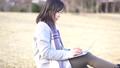 一個女人坐在公園的草坪上,使用筆記本電腦(慢) 73285742