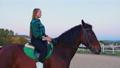 A teenage cowgirl on the horseback 73296477