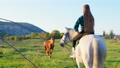 A teenage country girl riding a horse on a green field 73302273