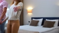 Happy young man and woman are falling on the bed in hotel room, slow motion. 73357517