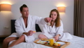 Young couple in bathrobes having a breakfast together in bed in hotel room. 73357518