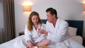 Young couple in bathrobes having a breakfast together in bed in hotel room. 73357520