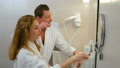 Young couple in bathrobes cleaning teeth together in bathroom before mirror. 73358659