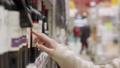 Woman selecting wine bottle in supermarket 73361430