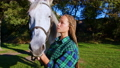 A teenage cowgirl stroking a horse 73371629