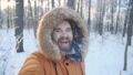 Winter tourism and hiking concept. Young bearded man taking selfie in the forest 73394082