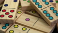 closeup abstract of wooden domino pieces with colorful pips (dots) rotating on turntable 73527628