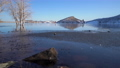 Winter view of a lake at foothills of Rocky Mountains with a distant stand up paddler 73527630