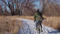 male cyclist is commuting by bike in winter scenery along the Poudre River in Fort Collins 73527637