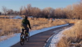 male cyclist is commuting by bike in winter scenery along the Poudre River in Fort Collin 73527638