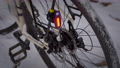 flashing rear light mounted on a touring bike against snowy trail 73527640