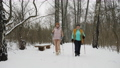 Women practice Nordic walking in a snowy forest 73553558