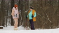 A young woman trainer explains to an elderly woman the technique of Nordic walking in a snowy forest 73553559