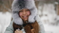 Portrait of attractive smiling caucasian teenage girl in winter fur hat outdoors 73564275