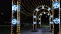 Colorful glowing round arch tunnel in a city park. Concept. Christmas and New Year eve on a winter evening with a figure made of shining garland. 73632038