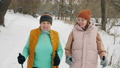 Happy aged woman with daughter practice Nordic walking in winter in nature 73667096
