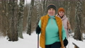 An elderly woman with her middle-aged daughter are engaged in Nordic walking in the winter 73667103