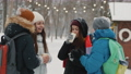 Happy teenagers spend time together in snowy weather, drinking warm drinks from paper cups 73667755