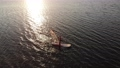 Aerial view of a sportive young woman learning to fly a windsurf board. Sunset workout. Low key 73694856