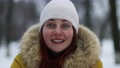 Close up portrait of woman in a hat, in warm red jacket smiling at the camera in winter in the forest 73698703