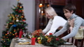 Side view of son helping mother putting Christmas decoration on celebration table. Happy positive Caucasian boy and woman decorating house on New Years' eve. Beauty and happiness. 73707820