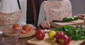 Unrecognizable mother and son preparing healthful salad at home. Caucasian woman and boy cutting cucumbers and tomatoes for healthy meal indoors. Cinema FullHD ProRes HQ. 73707883
