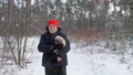 Bearded pensioner walks along snowy road holding dog 73708868