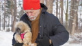 Bearded pensioner hides furry dog in winter coat close 73708870