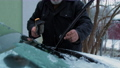 Aged man hands remove ice from black wipers of automobile 73709282