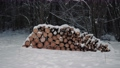 Panorama firewood stacked in a row outdoors on the background winter forest. A stack of folded chopped wood lies in the snow 73757591