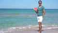 Happy man having fun on the beach and eating watermelon 73760721
