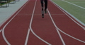 Crop view of disabled male person with prosthetic running blade at track on sports field. Amputee 73792776