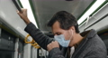 Side view of guy in medical mask having cough and looking ill in bus. Male person in wireless 73792795