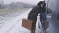 Woman hitchhiker with vintage suitcase talking with driver 73794303