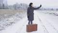 Woman hitchhiker holding up smartphone trying to get a signal 73794334