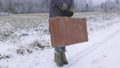 Woman with vintage suitcase on road in winter 73794335