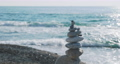Pyramid of stones on the beach. Heap of pebbles on rocky beach on sea surf background. Man-made structure. 73797262