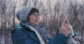 Woman makes online video-call on smartphone from winter forest. Wireless technology. Live broadcast. 73797271