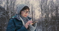 Woman texting and scrolling on smartphone in winter forest. Wireless technology. Online message. 73797272