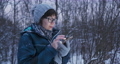 Woman texting and scrolling on smartphone in winter forest. Wireless technology. Online message. 73797273
