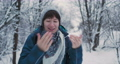 Woman warms her cold hands with breath Fun in snowy winter forest. Woman laughs as she walks through wood. Sincere emotions. 73797274