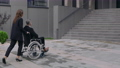 Stylish woman in suit pushing wheelchair with man coworker and stopping before office building 73805811